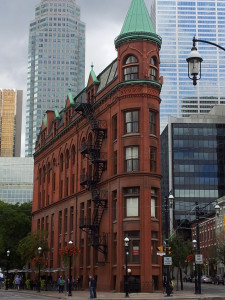 Flatiron building with red brick and green roof